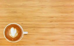 Vue supérieure d'un café avec le modèle de coeur dans une tasse blanche sur le fond en bois Photos libres de droits