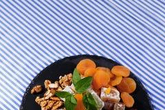 Vue supérieure d'un désert Abricots, noix et menthe secs d'un plat de plaisir turc sur un fond rayé Copiez l'espace Photos stock