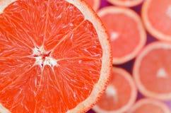 Vue supérieure d'un fragment de la tranche rouge de pamplemousse sur le fond de beaucoup de tranches brouillées de pamplemousse U illustration stock