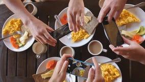 Vue supérieure d'un groupe d'amis prenant le petit déjeuner dans un café à la table en bois, photographiant une omelette, les pai Photos libres de droits
