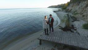 Vue supérieure d'un jeune couple embrassant tendrement à la rivière Une position attrayante de couples sur une plate-forme en boi banque de vidéos