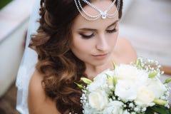 Vue supérieure d'un plan rapproché d'une jeune mariée grecque admirant son bouquet blanc des roses, abaissé ses yeux vers le bas, photographie stock