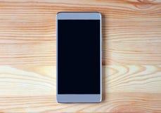 Vue supérieure d'un smartphone vide noir d'écran d'isolement sur la table en bois brun clair photographie stock libre de droits
