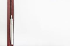 Vue supérieure d'un stylo se trouvant entre deux pages de papier blanches Images stock