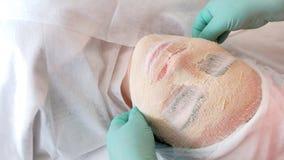Vue supérieure d'une femme dans une gaze hydratant le masque qui se repose dans un salon de beauté L'esthéticien fait un masqu photographie stock