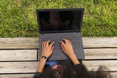 Vue supérieure d'une jeune femme afro-américaine à l'aide de l'ordinateur portable Dos de vert Photographie stock