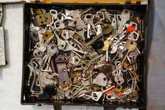 Vue supérieure d'une pile de différentes clés rouillées antiques dans le noir Photographie stock