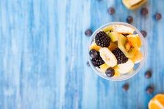 Vue supérieure d'une tasse pleine des fruits délicieux au-dessus d'un bureau en bois image libre de droits