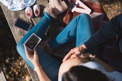 Vue supérieure de bel enceinte et de son mari touchant le ventre et regardant l'image d'ultrason Concept de grossesse, soins de s photographie stock libre de droits