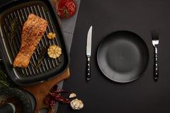 vue supérieure de bifteck saumoné grillé disposé sur la planche à découper, la sauce et les couverts en bois sur le dessus de tab images libres de droits