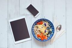 Vue supérieure de bol de petit déjeuner, de téléphone intelligent et de comprimé numérique photographie stock libre de droits