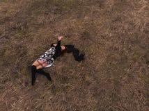 Vue supérieure de bourdon aérien d'une fille se situant dans un domaine détendant et dansant Porter une robe avec des bas photo stock