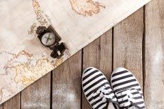 Vue supérieure de boussole, de carte du monde et de chaussures rayées sur la table en bois Image stock
