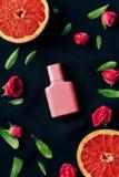 vue supérieure de bouteille de parfum avec les bourgeons et les tranches roses de pamplemousse autour photos libres de droits