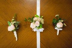 Vue supérieure de boutonniere de mariage pour le marié et les demoiselles d'honneur sur le fond en bois, l'espace libre Copiez l' Images stock