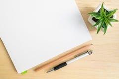 Vue supérieure de bureau avec le carnet ouvert sur la table en bois Photographie stock libre de droits