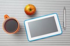 Vue supérieure de bureau avec le PC de comprimé, tasse de thé, pomme Photographie stock libre de droits