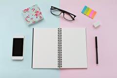 Vue supérieure de bureau d'espace de travail avec le carnet vide, les verres d'oeil, le téléphone intelligent et la papeterie de  Photo libre de droits