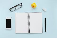 Vue supérieure de bureau d'espace de travail avec le carnet vide, les verres d'oeil, le téléphone intelligent, le canard et la pa Photo stock