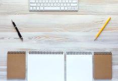 Vue supérieure de bureau en bois léger avec le clavier et la papeterie photos stock