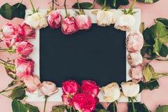 Vue supérieure de cadre faite à partir de belles roses roses et de cadre blanc vide Photos stock