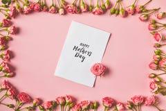 vue supérieure de cadre faite à partir de belles roses roses et de carte de voeux heureuse de jour de mères sur le rose images libres de droits