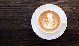 Vue supérieure de café de cappuccino d'art chaud de latte sur le fond en bois foncé de table photo libre de droits