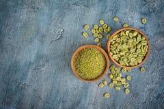 Vue supérieure de café non rôti vert vert avec les haricots moulus dans des cuvettes en bois photo stock