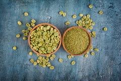 Vue supérieure de café non rôti vert vert avec les haricots moulus dans des cuvettes en bois images stock