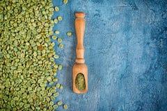 Vue supérieure de café non rôti vert vert avec les haricots moulus dans le scoop en bois images libres de droits