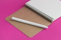 Vue supérieure de carnet ouvert avec le stylo-plume sur le fond rose Photo stock