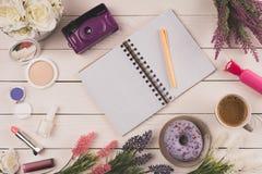 Vue supérieure de carnet ouvert vide avec le stylo, l'appareil-photo, les fleurs, les cosmétiques et la tasse de café avec le bei Images stock