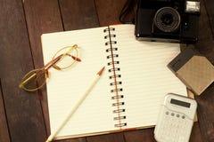 Vue supérieure de carnet, verres, crayons, calculatrices, appareils-photo Photo libre de droits