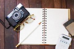 Vue supérieure de carnet, verres, crayons, calculatrices, appareils-photo Image stock