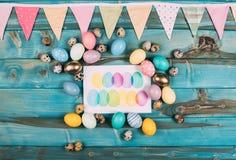 vue supérieure de carte de voeux heureuse colorée de Pâques avec les oeufs colorés autour sur le bleu photos stock