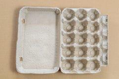 Vue supérieure de conteneur d'oeufs de carton sur un fond brun photos libres de droits
