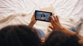Vue supérieure de deux amies s'asseyant sur le lit à la maison parlant sur le skype sur la tablette avec leur ami ayant des vacan Image libre de droits