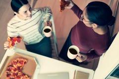 Vue supérieure de deux amis mangeant de la pizza et buvant du thé Photos libres de droits