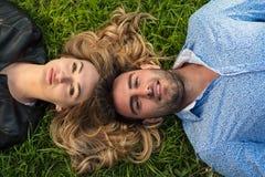 Vue supérieure de deux amis souriant tout en regardant vers le ciel comme ils s'étendant à l'herbe Photos libres de droits