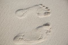Vue supérieure de deux empreintes de pas dans l'au sol de sable photos stock