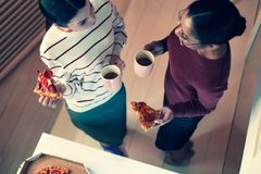 Vue supérieure de deux femmes appréciant la pizza et le thé Photos libres de droits