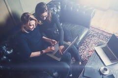 Vue supérieure de deux jeunes filles travaillant sur l'ordinateur et à l'aide des périphériques mobiles au grenier moderne Femme  Image libre de droits