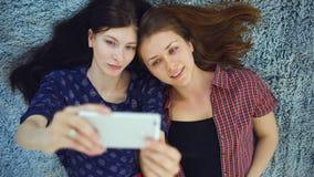 Vue supérieure de deux jolies filles dans des pyjamas faisant le portrait de selfie sur le lit dans la chambre à coucher à la mai Photographie stock