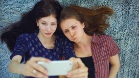 Vue supérieure de deux jolies filles dans des pyjamas faisant le portrait de selfie sur le lit dans la chambre à coucher à la mai Photos stock