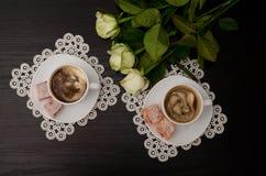 Vue supérieure de deux tasses de café avec du lait, plaisir turc sur une soucoupe, roses blanches Images stock