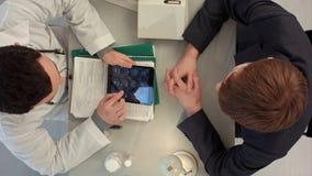 Vue supérieure de docteur passant en revue le rayon X avec le patient photos stock