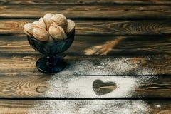 Vue supérieure de farine de blé de forme de coeur avec l'amour de lettre écrous de cuisson Photos libres de droits