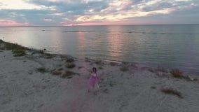 Vue supérieure de femme avec le maquillage lumineux dans une danse rose de robe avec des bombes fumigènes sur la banque de la riv banque de vidéos