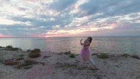 Vue supérieure de femme douce avec le maquillage de brillant dans une danse rose de robe avec des bombes fumigènes sur la banque  banque de vidéos