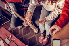 Vue supérieure de fille bouclée essayant d'accorder la guitare se reposant près des amis photos libres de droits